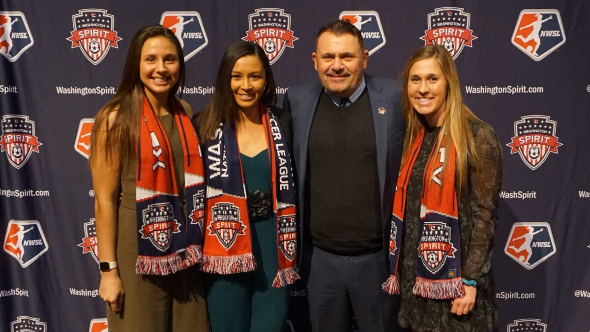 Richie Burke, the new Washington Spirit coach, poses with three of the NWSL team's.