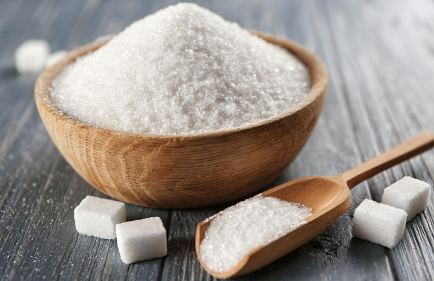 Sugar on a bowl and spoon. Cube sugar